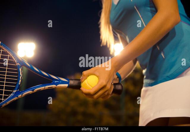 Closeup portrait of a female tennis player holding racket and ball - Stock-Bilder
