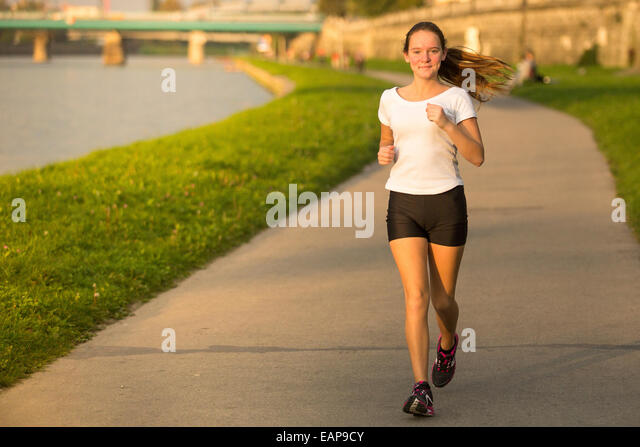Girl runner in the urban environment. Healthy lifestyle. - Stock Image
