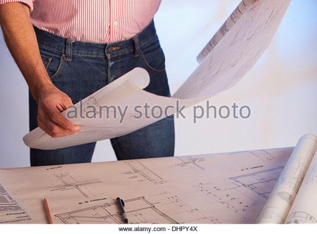 Man holding blueprint architectural drawing plan - Stock Image