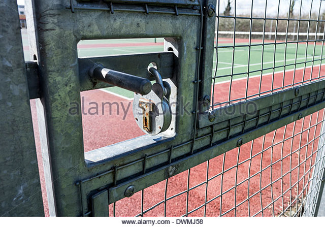 Padlocked gate to tennis court - Stock Image
