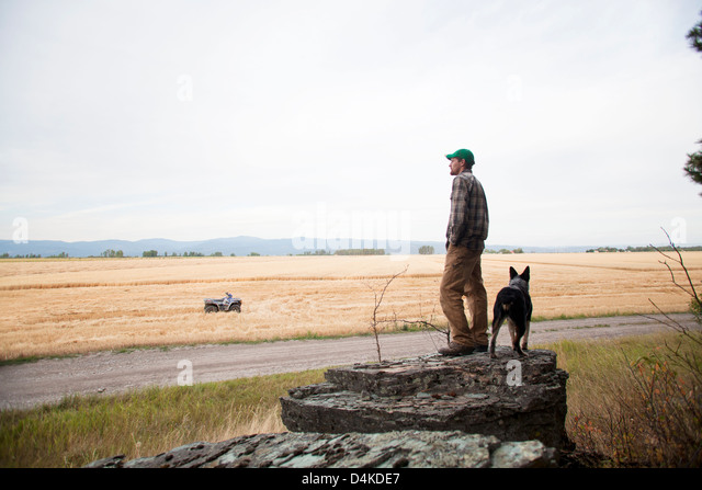 Man with dog on rock formation - Stock Image