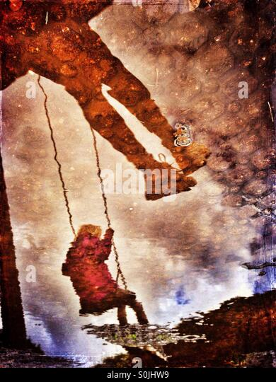 Reflections in muddy puddle of two girls on swings - Stock-Bilder