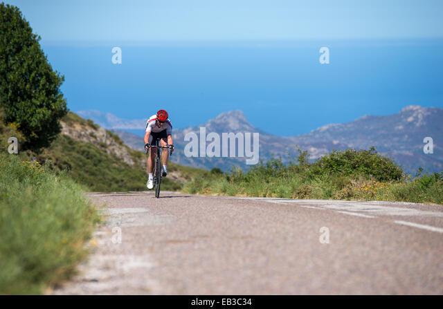 France, Corsica, Road biker racing towards camera - Stock Image