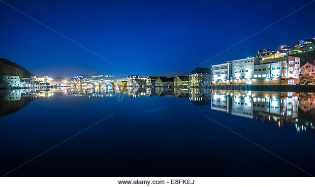 Norway, Rogaland, Panorama of Egersund inner harbor by night with water reflection - Stock Image