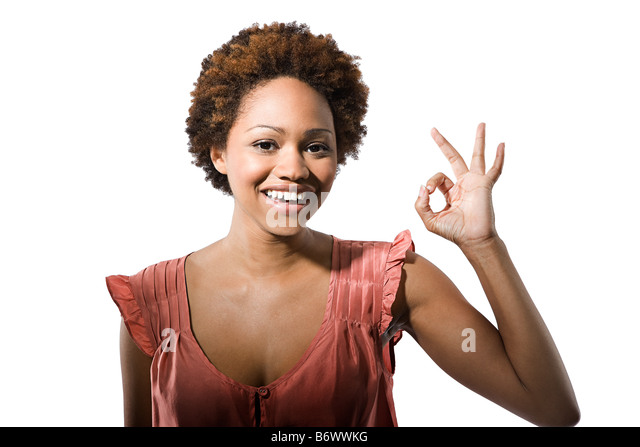 Portrait of young woman giving the ok sign - Stock Image