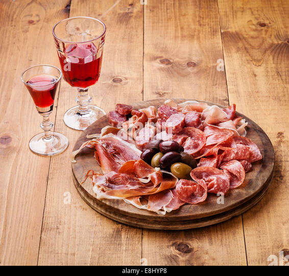 Cold meat plate and wine on wooden background - Stock Image
