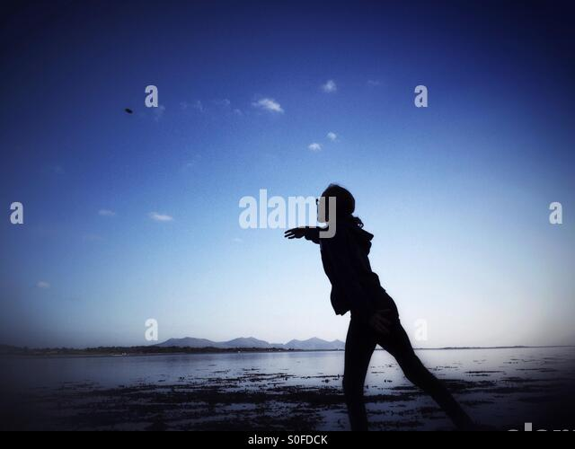 Young girl throwing stone into sea on Anglesey in Wales - Stock Image
