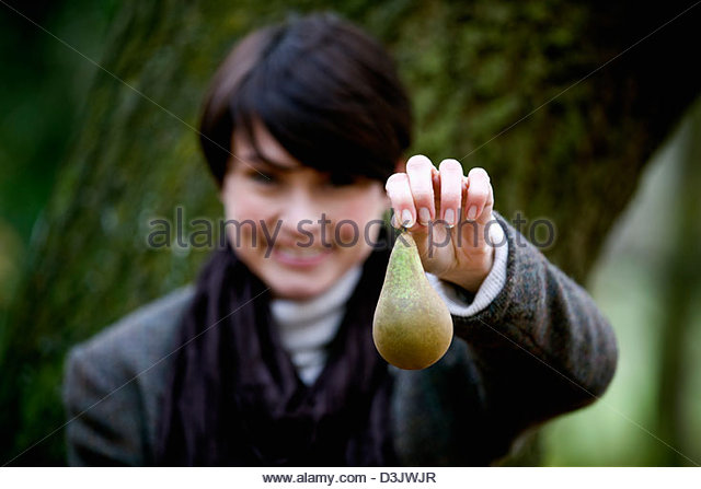 A woman holding a pear in front of her - Stock Image