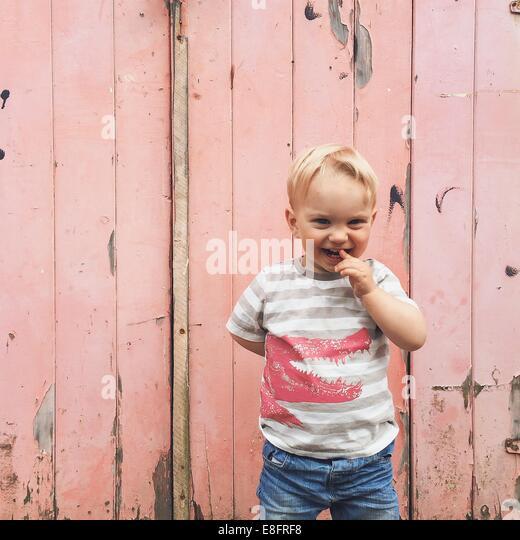 Smiling boy standing outside garage door - Stock Image