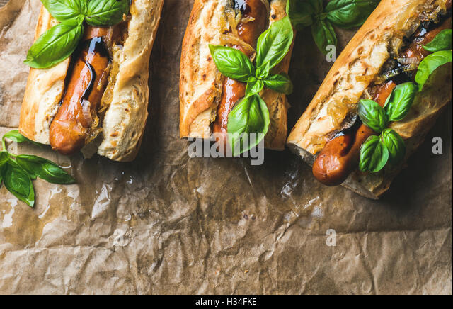 Homemade grilled sausage dogs in baguette on baking paper - Stock Image
