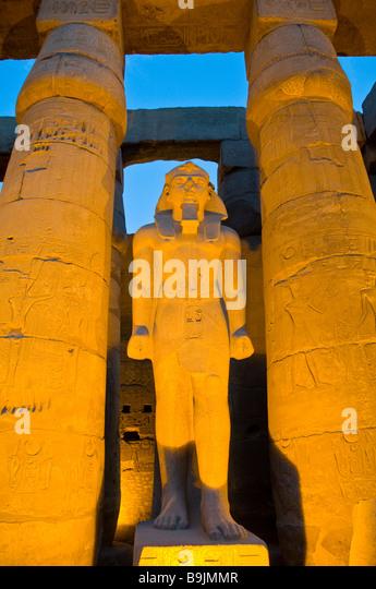 Luxor Temple Egypt twilight illuminated lighted pharoah sculpture located between two tall columns Egyptian tourist - Stock Image