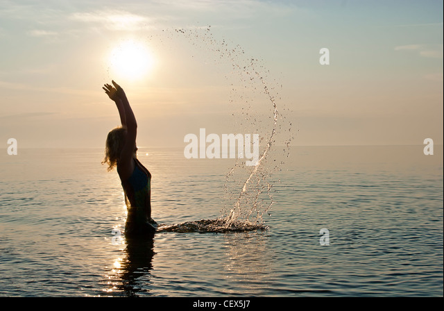 Girl in clothe swimming - Stock Image