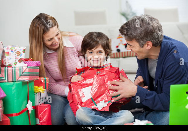 Boy And Parents Opening Christmas Present - Stock Image