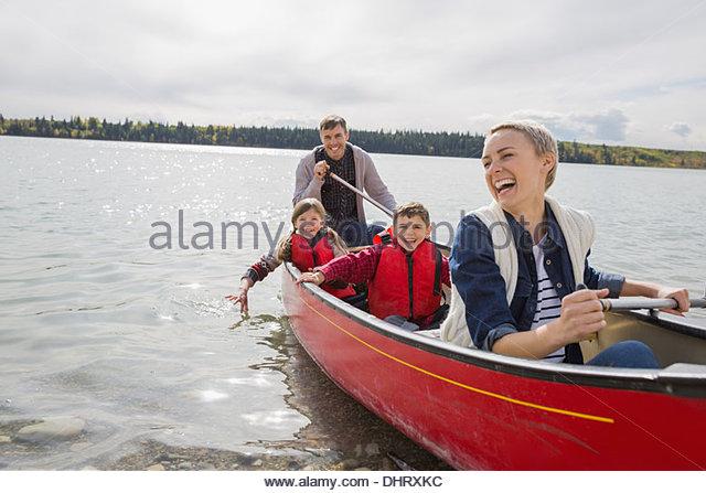 Happy family canoeing on lake - Stock Image