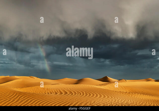 Sahara sand dunes with stormy, cloudy sky and rainbow. - Stock Image