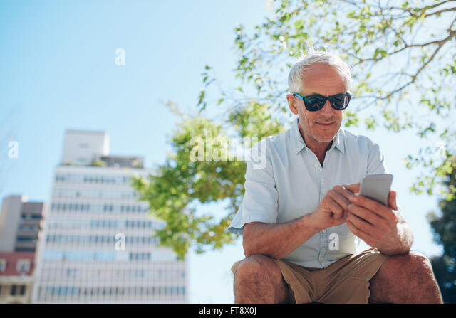Low angle view of mature man sitting outdoors using mobile phone. Mature tourist resting outside in the city and - Stock-Bilder