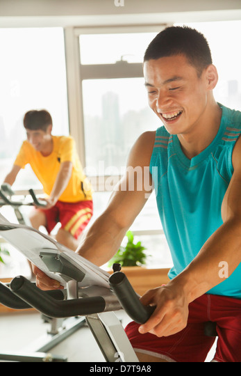 Young men on stationary bikes exercising in the gym - Stock Image