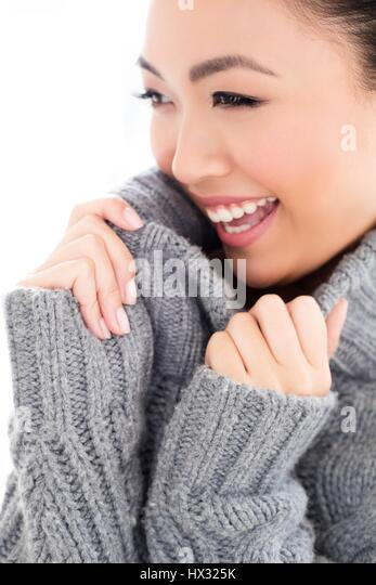 MODEL RELEASED. Young Asian woman wearing grey knitted sweater, portrait. - Stock-Bilder