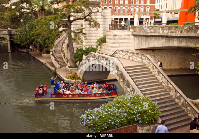 San Antonio River Walk texas tour boat passing under bridge one level below street traffic - Stock Image