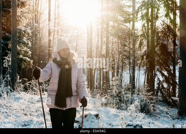 Mid adult woman nordic walking in snow covered forest - Stock Image