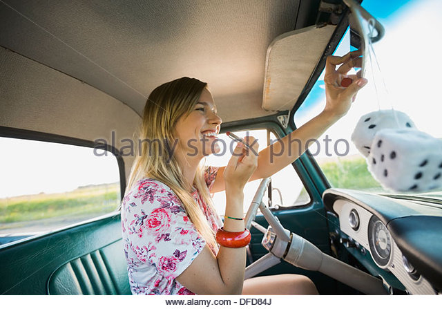 Woman applying lipstick in pick-up truck - Stock Image
