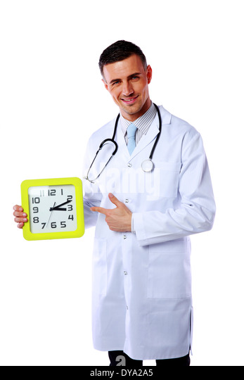 Portrait of a male doctor showing on clock over white background - Stock Image
