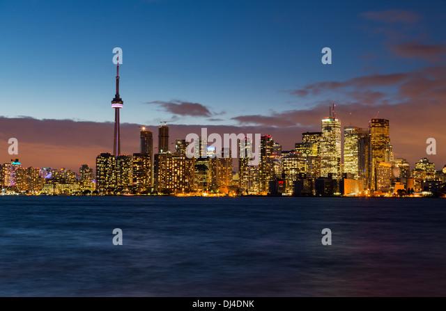 Toronto skyline across Lake Ontario, Canada at night / dusk - Stock Image
