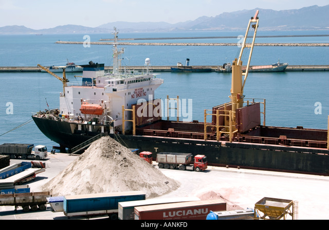 Trucks Cranes and Ships loading salt at Cagliari Harbour, Sardinia, - Stock Image