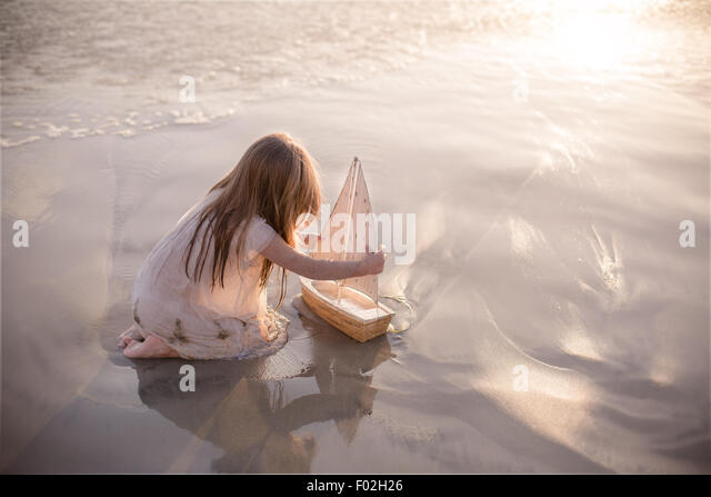 Girl sitting on the beach playing with a boat at sunset - Stock Image