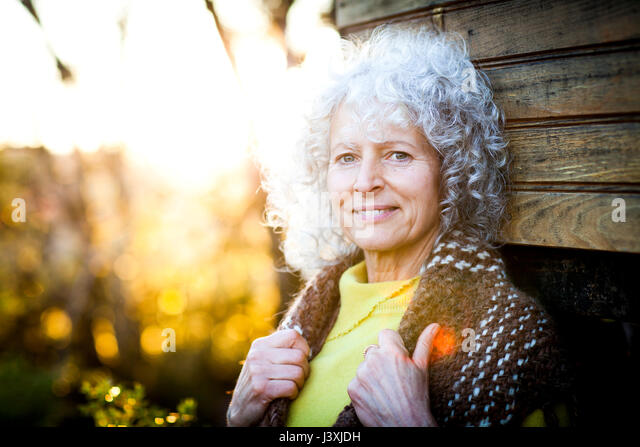 Portrait of mature woman with grey hair leaning against woodland treehouse at sunset - Stock Image