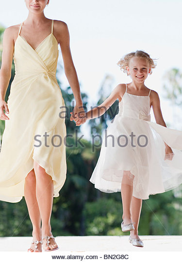 Flower girl holding hands with mother - Stock Image