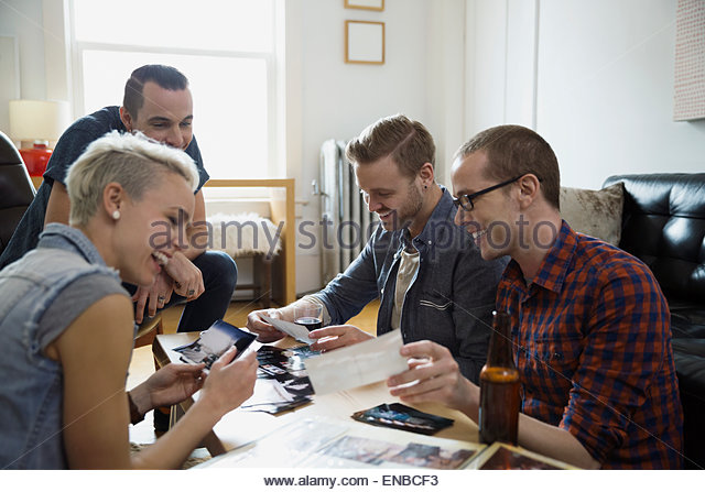 Friends looking at photographs drinking beer living room - Stock Image