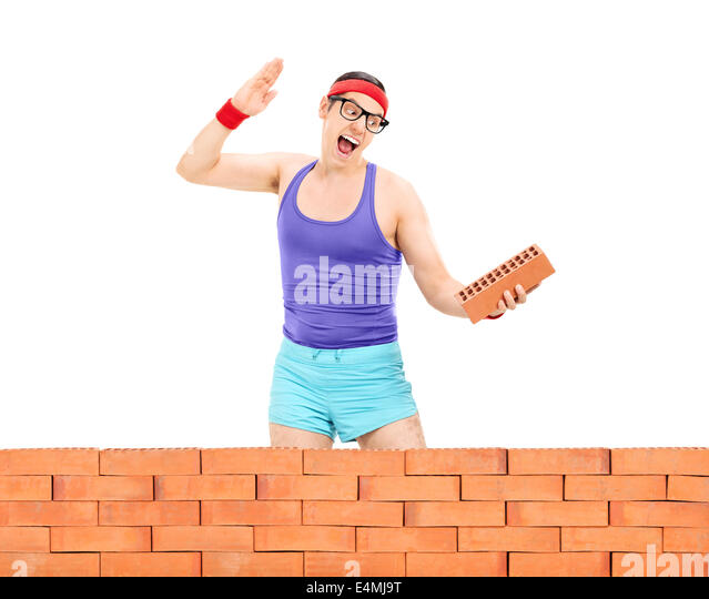 Man smashing a brick behind a brick wall - Stock Image