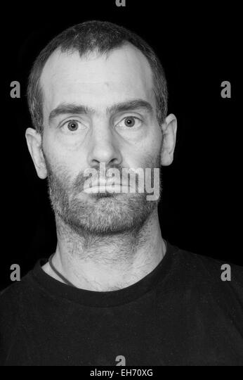 black and white portrait of a rugged grizzled middle aged man with black t-shirt on black background - Stock Image