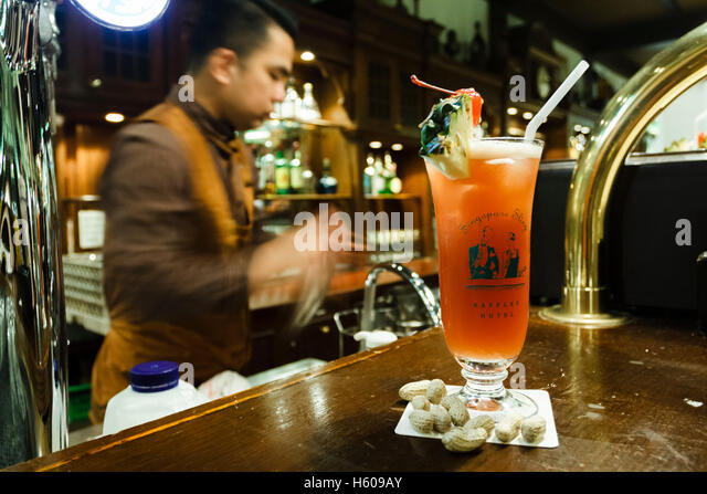 A barman mixes a Singapore Sling in the Long Bar, Raffles hotel, Singapore - Stock Image