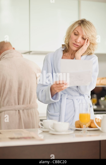 Stressed woman reading mail in bathrobe - Stock Image