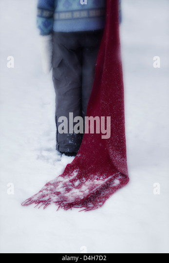 a girl with a red scarf in the snow - Stock Image