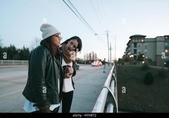 Young ethnic girls standing on overpass bridge - Stock Image