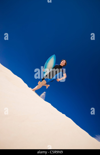 Young man running across surf dunes to the Ocean with surfboard. - Stock-Bilder