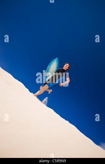 Young man running across surf dunes to the Ocean with surfboard. - Stock-Bilder