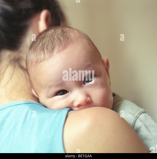 baby looking over mother's shoulder - Stock Image