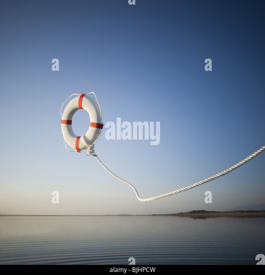life preserver being thrown into a lake - Stock Image