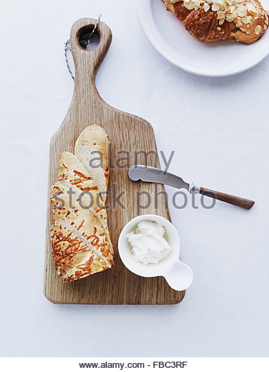 Baguette on cutting board served with cream cheese - Stock Image