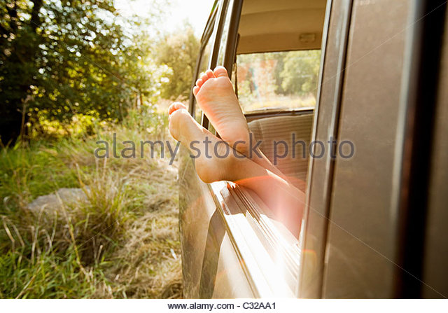 Bare feet sticking out of a car window - Stock Image