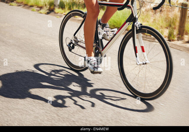 Low section image of woman riding bicycle on country road. Cropped image of female athlete cycling. Action shot - Stock Image