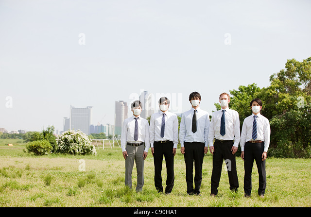 Businessmen in a row wearing pollution masks - Stock Image