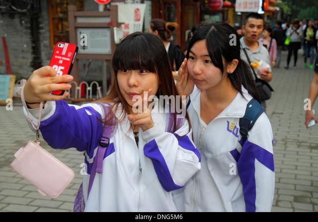 Beijing China Dongcheng District Nanluoguxiang hutong historic shopping Asian teen girl friends smartphone student - Stock Image