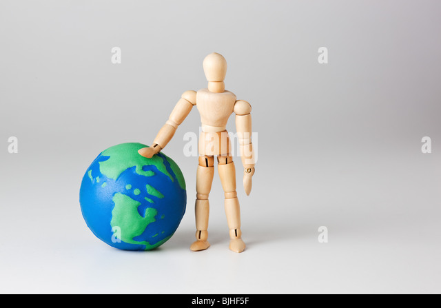 mannequin with toy earth in studion - Stock Image