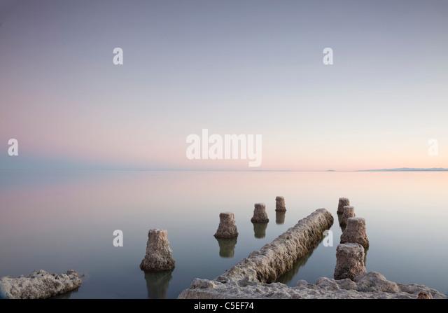 Posts of old jetty on Salton Sea at twilight. - Stock Image