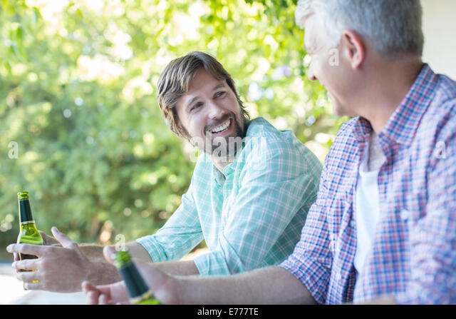 Father and son drinking outdoors - Stock Image